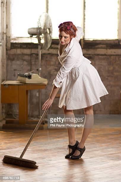 Woman in vintage dress sweeps floor