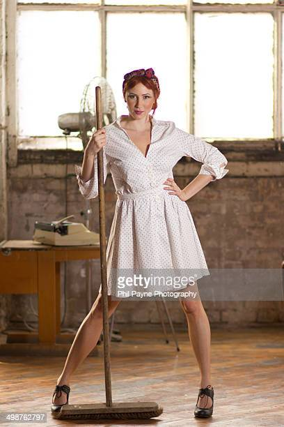 Woman in vintage dress with broom