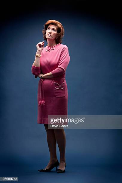 woman in vintage pink dress looking up - one mature woman only stock pictures, royalty-free photos & images