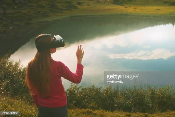 Woman in virtual reality glasses standing near a lake
