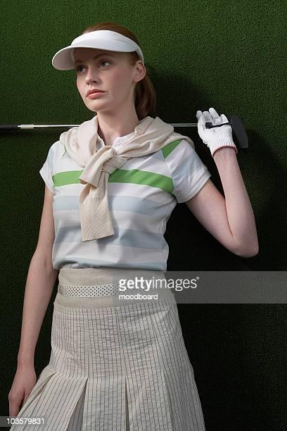 Mulher no visor segurando golf club atrás ombros Retrato