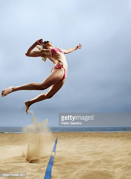 woman in volleyball spiking postion, side view - beachvolleybal stockfoto's en -beelden