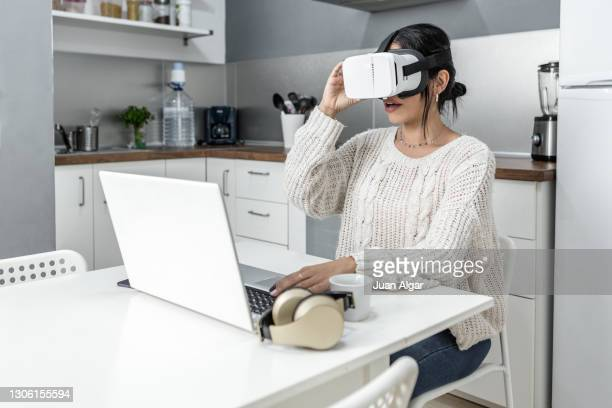 woman in vr goggles at table - seulement des adultes photos et images de collection