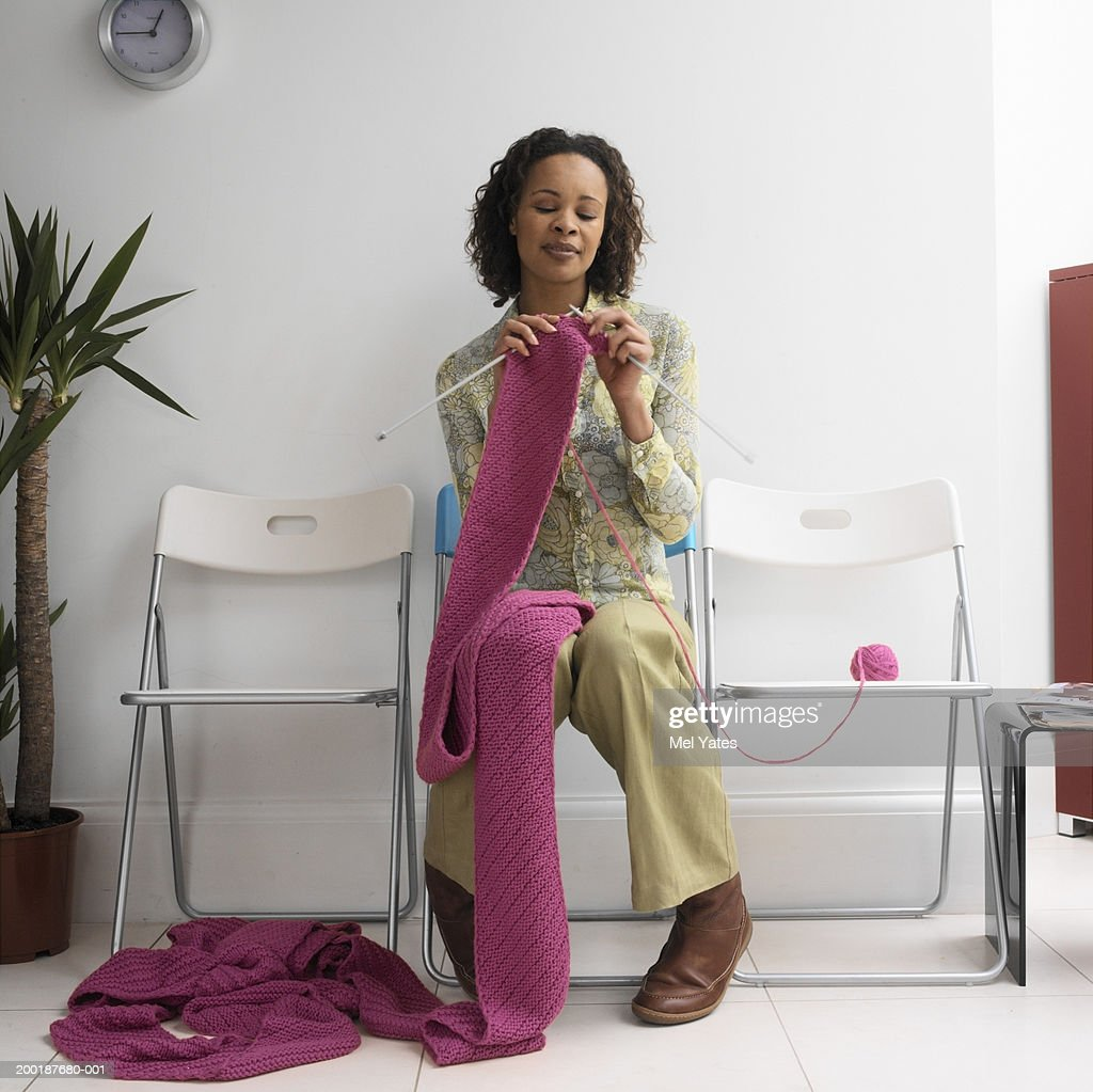 Woman in waiting room, sitting in row of chairs, knitting : Stock Photo