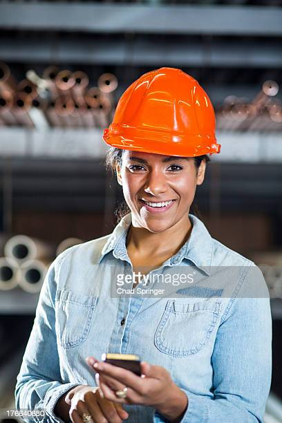 Woman in warehouse holding smartphone