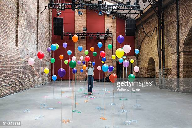 woman in warehouse with colourful balloons - contrasti foto e immagini stock