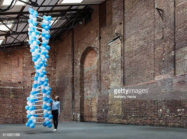Woman in warehouse with DNA made of balloons