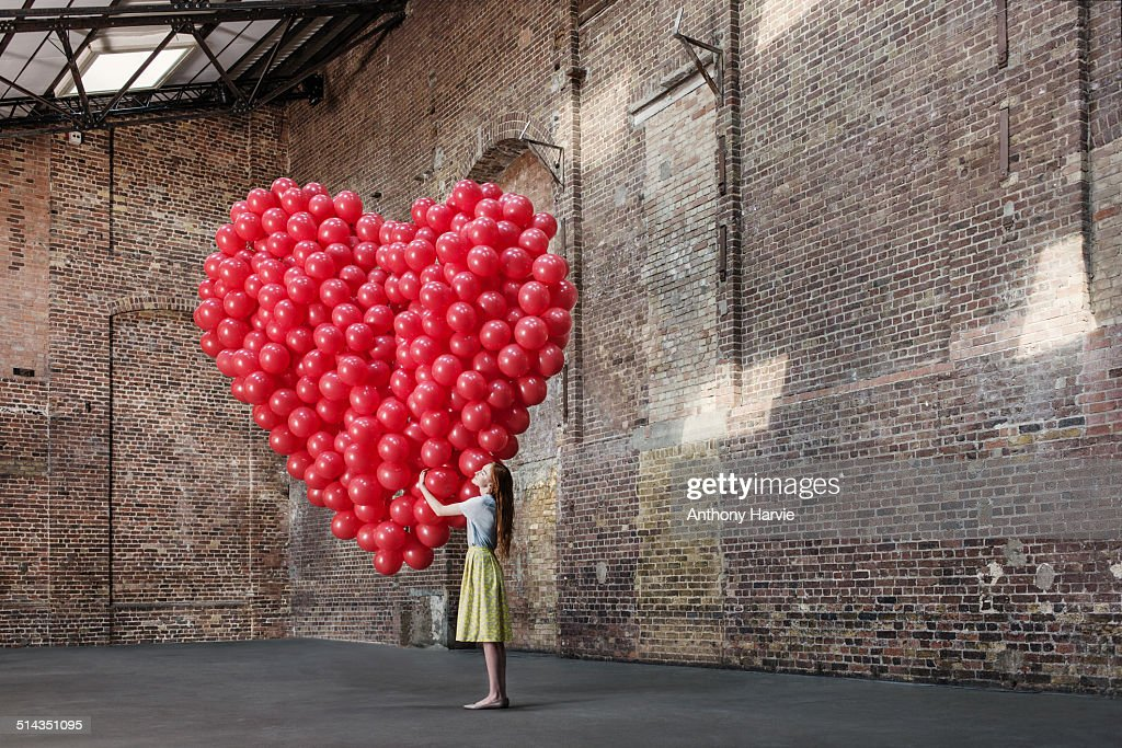 Woman in warehouse with heart made of balloons : Stock-Foto