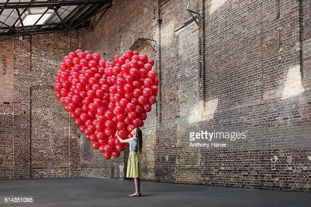 woman in warehouse with heart made of balloons - love emotion stockfoto's en -beelden