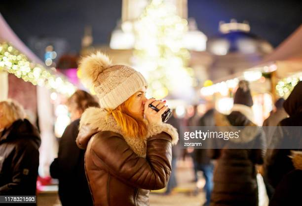 woman in warm clothes drinking tea on christmas market - gendarmenmarkt stock pictures, royalty-free photos & images
