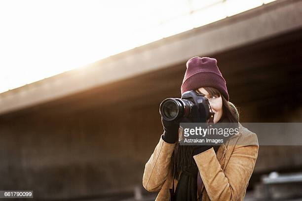 Woman in warm clothing photographing with camera outdoors