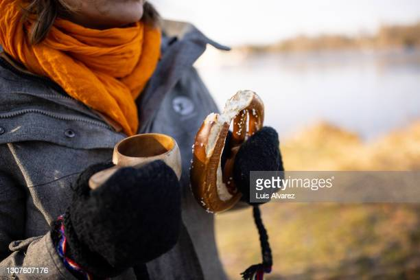 woman in warm wear having coffee and bread in forest - warm clothing stock pictures, royalty-free photos & images