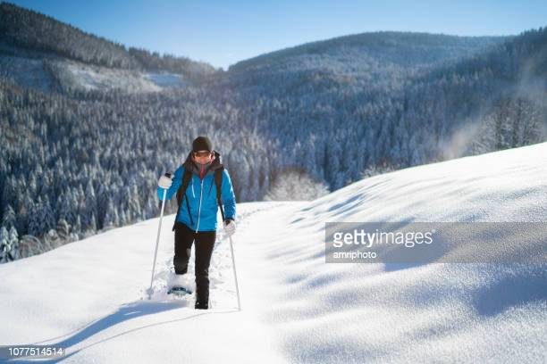 woman in warm winter sport clothes enjoying snowshoe hike in deep snow on sunny winter day in rural landscape - winter sport stock pictures, royalty-free photos & images
