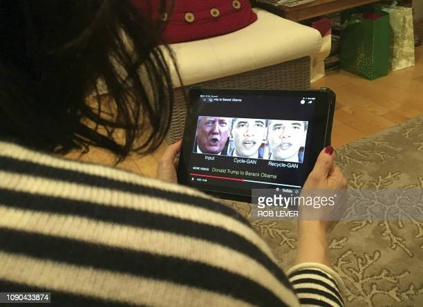 A woman in Washington DC views a manipulated video on January 24 that changes what is said by President Donald Trump and former president Barack...