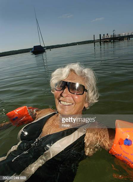 Woman in water, wearing arm bands and sunglasses, smiling, close up