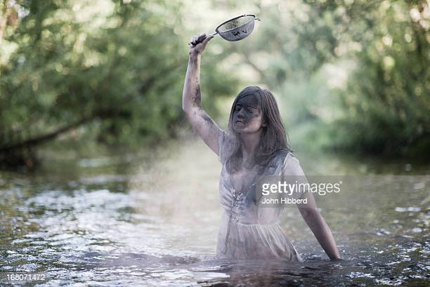 woman in water with sieve - waist deep in water stock pictures, royalty-free photos & images