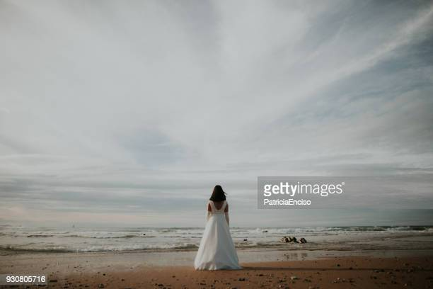 woman in wedding dress at beach - runaway stock photos and pictures
