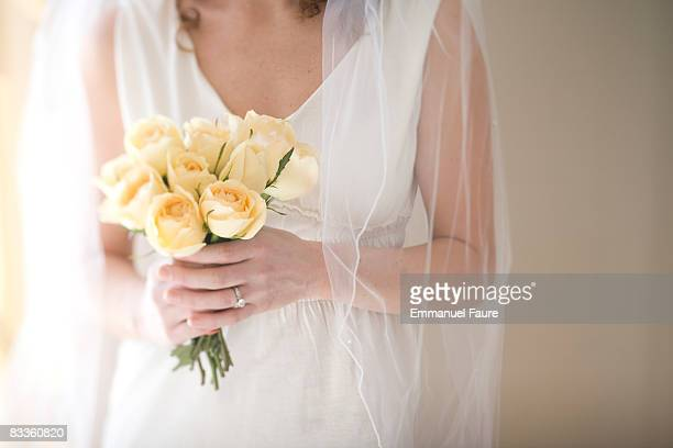 Woman in wedding dress holding bouquet