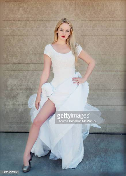 A woman in wedding dress poses with leg out like Angelina Jolie