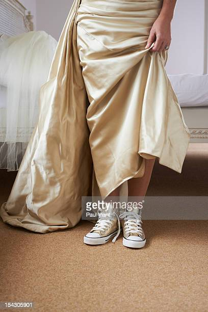 a woman in wedding dress with baseball boots - gold shoe stock photos and pictures