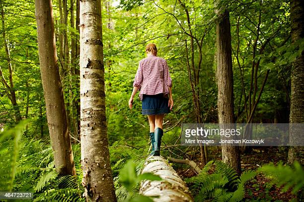 A woman in wellingtons walking along a fallen tree trunk,in woodland.