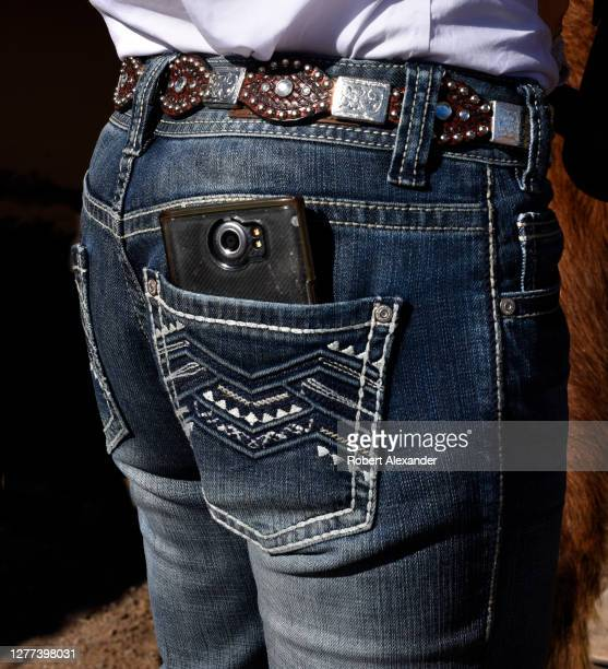 Woman in western attire carries her smartphone in her back pocket.