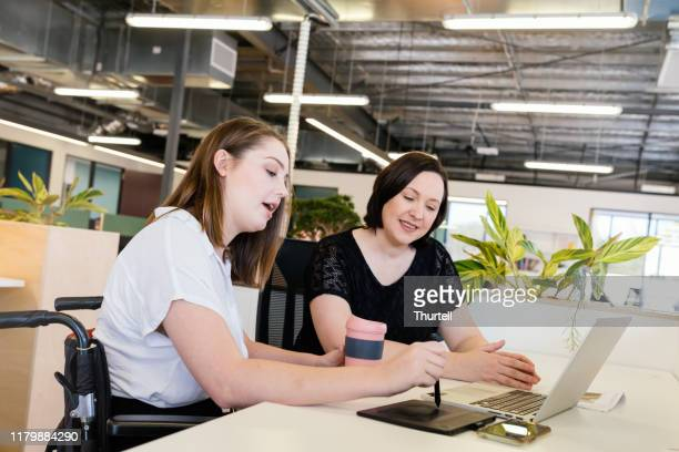 woman in wheelchair collaborating in modern office - accessibility stock pictures, royalty-free photos & images