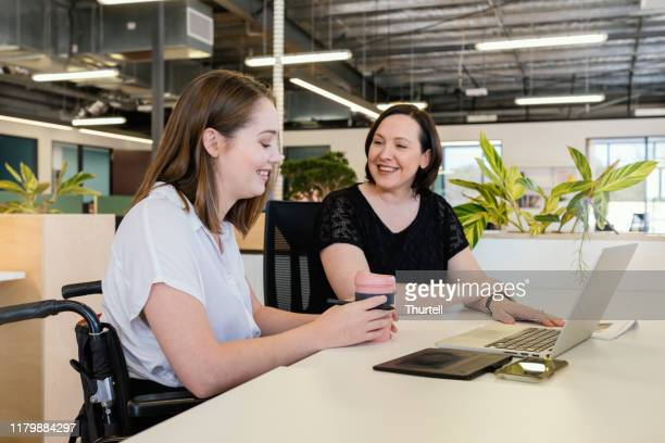 woman in wheelchair collaborating in modern office - white collar worker stock pictures, royalty-free photos & images