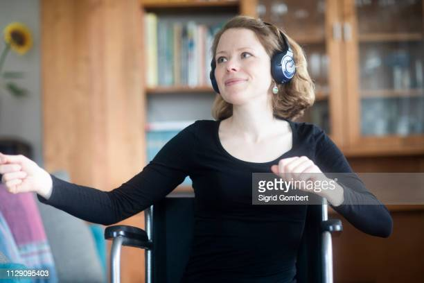 woman in wheelchair dancing to music on headphones - sigrid gombert stock pictures, royalty-free photos & images
