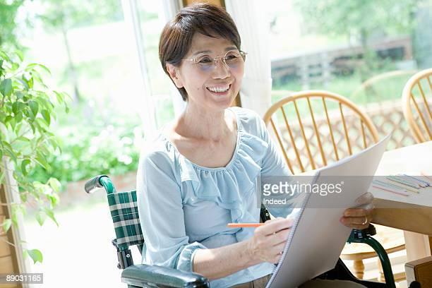 Woman in wheelchair drawing on sketchbook
