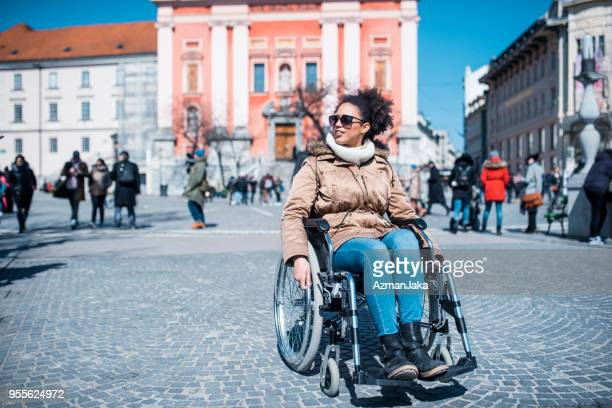 Woman in wheelchair enjoying the spring weather in the city