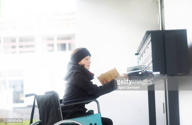 woman in wheelchair getting post from post box - sigrid gombert imagens e fotografias de stock