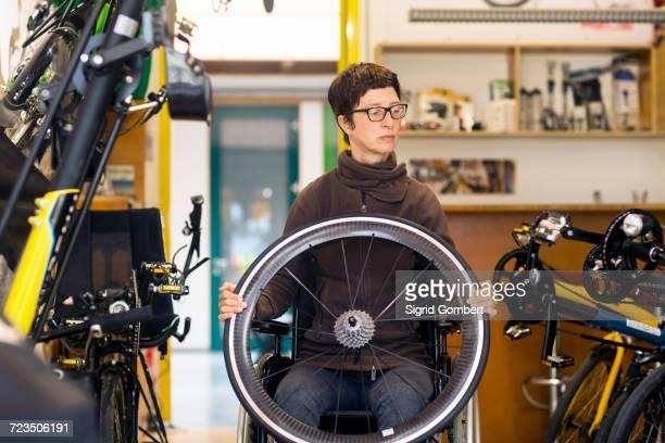 woman in wheelchair in bicycle repair shop, holding bicycle wheel - sigrid gombert stock-fotos und bilder