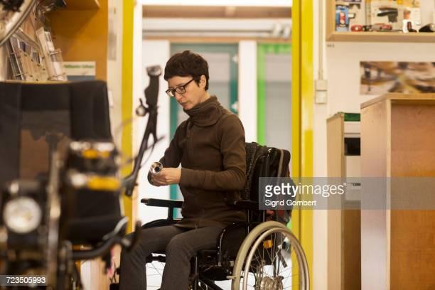 woman in wheelchair in bicycle repair shop - sigrid gombert fotografías e imágenes de stock