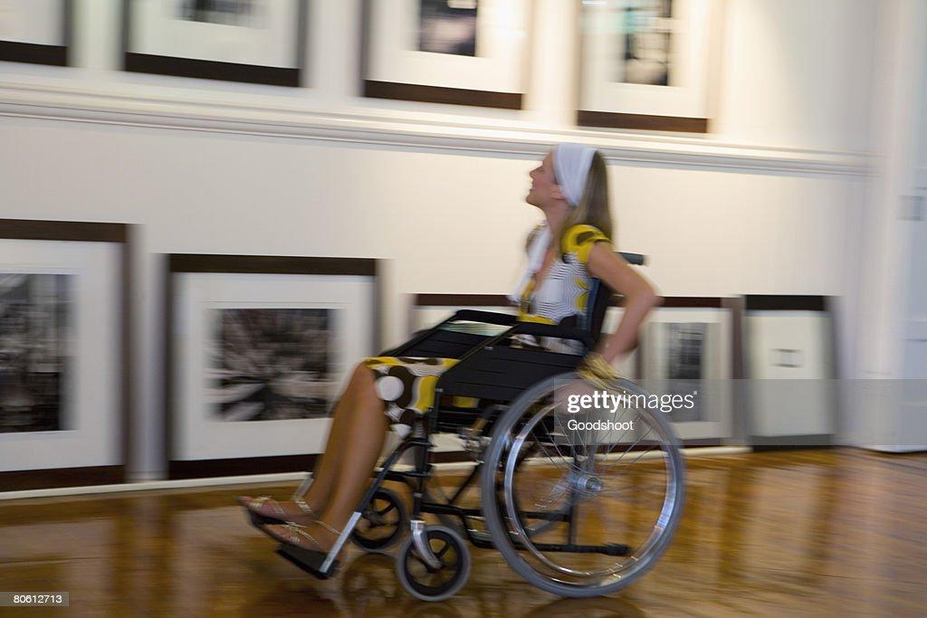Woman in wheelchair in gallery : Foto de stock