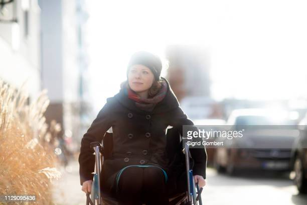 woman in wheelchair in street - sigrid gombert stock pictures, royalty-free photos & images