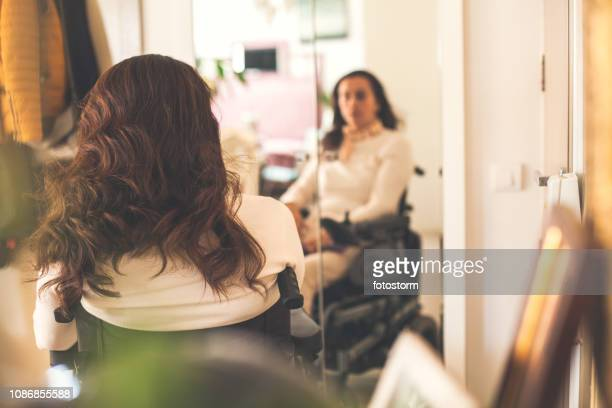 Woman in wheelchair looking at her reflection in the mirror