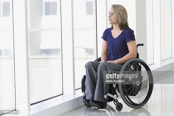 Frau im Rollstuhl mit Blick aus dem Fenster