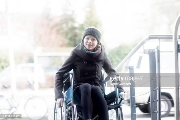 woman in wheelchair moving up ramp - sigrid gombert fotografías e imágenes de stock