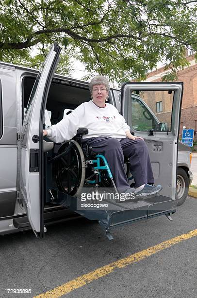 Woman in wheelchair on van lift being lowered to the street