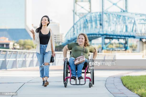 woman in wheelchair on waterfront with hispanic friend - of deformed people stock pictures, royalty-free photos & images