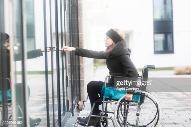 woman in wheelchair opening door to building - sigrid gombert imagens e fotografias de stock