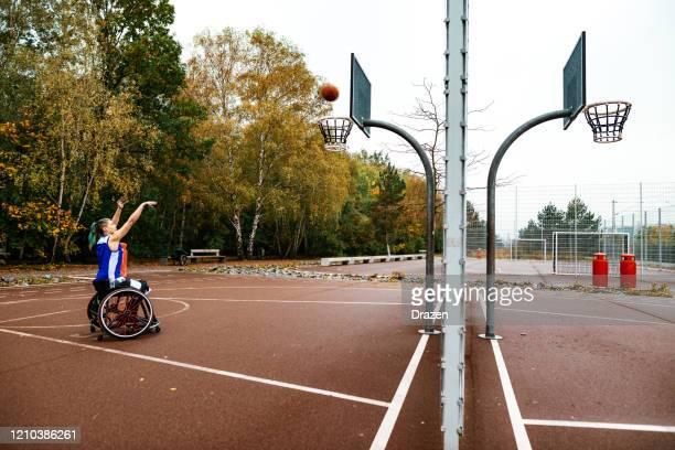 donna in sedia a rotelle che gioca a basket - tiro libero - femminilità foto e immagini stock