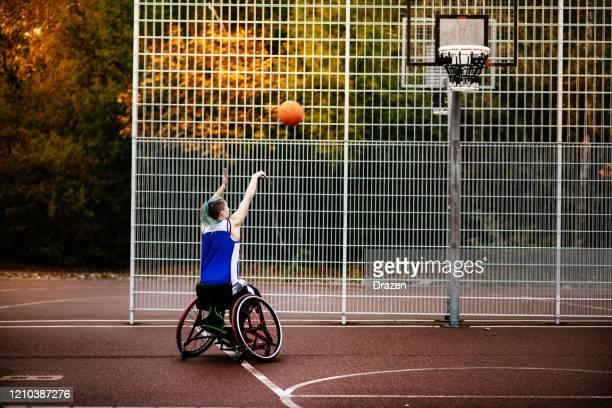 donna in sedia a rotelle che gioca a basket - femminilità foto e immagini stock