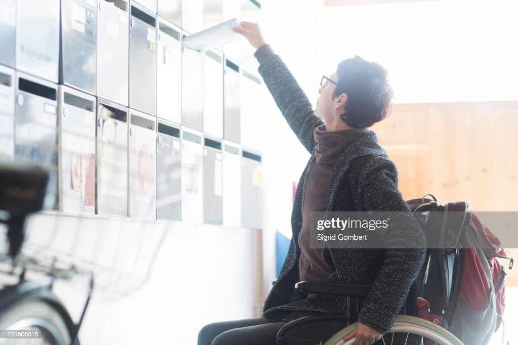 Woman in wheelchair, reaching up, posting mail through letterbox : Stock Photo