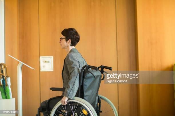 woman in wheelchair, reading sign at office entrance - sigrid gombert fotografías e imágenes de stock