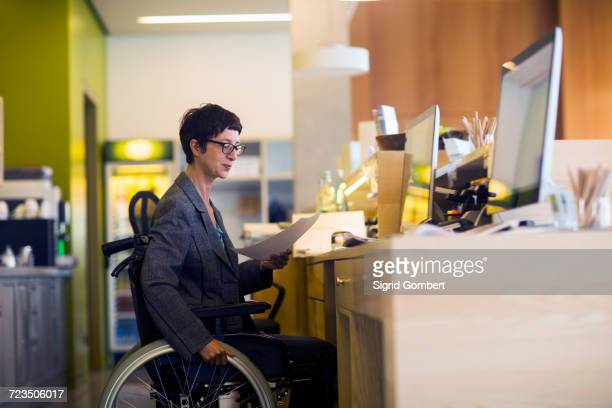 Woman in wheelchair, sitting at desk, looking at document