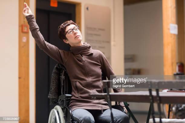 woman in wheelchair, sitting at table, raising arm to get attention - sigrid gombert stock-fotos und bilder