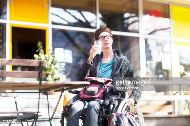 woman in wheelchair, sitting outside cafe, drinking cold drink - sigrid gombert fotografías e imágenes de stock