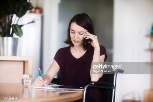 woman in wheelchair using cellphone and taking notes - sigrid gombert 個照片及圖片檔